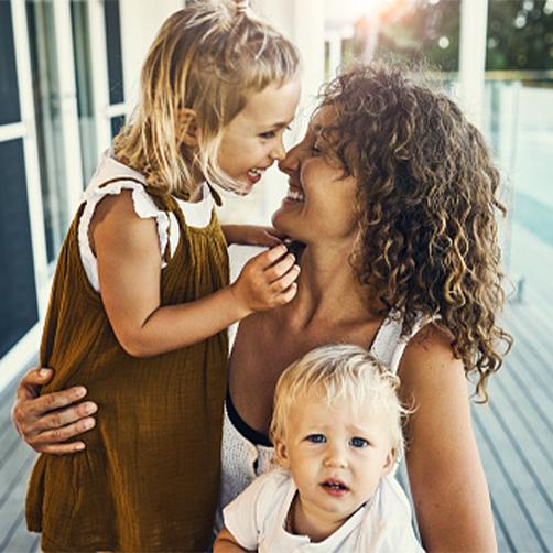 Femme avec ses deux enfants dans les bras