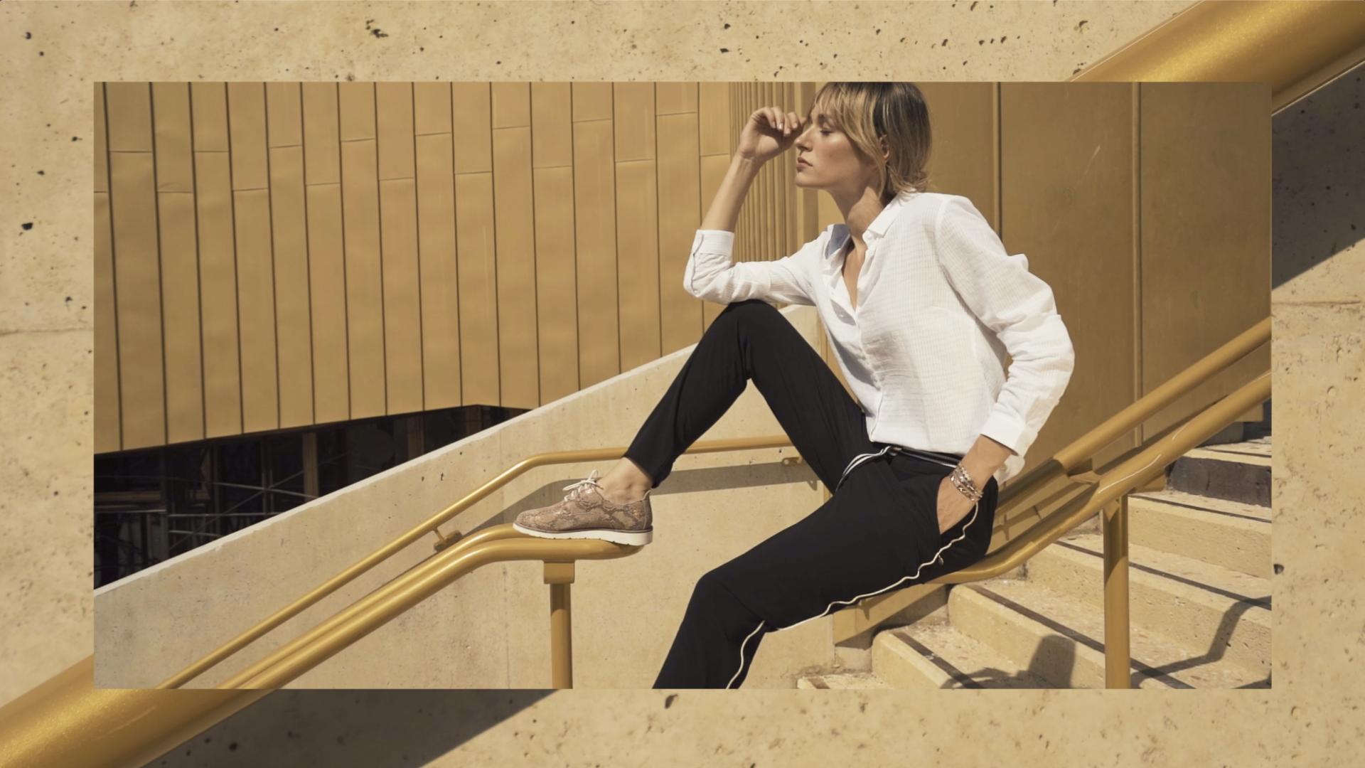 Femme décontractée qui pose dans des escaliers assise sur une rambarde